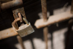 Iron lock. Old rusty iron lock closed on a gate with bars Stock Photos