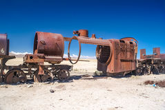Iron machine in Bolivia. Photo of large iron machine on railway surrounded by lonely sandy plains near Salar de Uyuni in Bolivia Royalty Free Stock Image