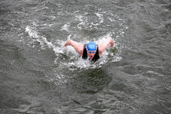 Iron man  swimmer in cap and wetsuit breathing performing butterfly stroke Stock Photography