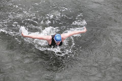 Iron man - swimmer performing the butterfly stroke in dark ocean water. Dynamic and fit swimmer in cap and wetsuit breathing performing the butterfly stroke in Royalty Free Stock Photos