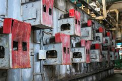 Iron metal red cabinets for perforated electric grid equipment located on a wall at an industrial petrochemical chemical refinery stock image