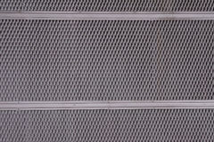 Iron metal sheet plate cladding with perforated holes in a geometric pattern and a rust effect. Grey Stock Images