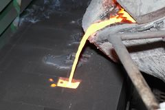 Iron molten metal pouring in sand mold. Green sand process stock image