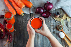 Iron mug with carrot juice in female hands Stock Photos