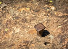 Iron nail in the rock with near the hole of an extracted nail.  Royalty Free Stock Photos