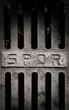 Iron old roman manhole cover. Detail with spqr sign Royalty Free Stock Photos