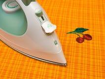 Iron on orange cloth Royalty Free Stock Image