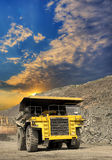 Iron ore mining. Heavy dump truck transporting iron ore from the opencast on sunset Stock Photography