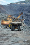 Iron ore mining. Heavy dump trucks being loaded with iron ore on the opencast by the excavator Stock Photos