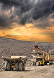 Iron ore mining. Heavy dump trucks being loaded with iron ore on the opencast on stormy sunset Royalty Free Stock Photo