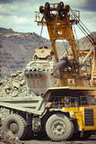 Iron ore mining. Heavy mining truck and excavator developing the iron ore on the opencast mining site Royalty Free Stock Photography
