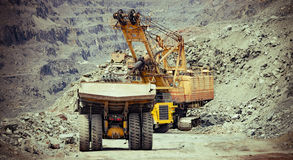 Iron ore mining. Heavy mining trucks and excavator working on the iron ore opencast mining site Stock Image