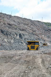 Iron ore mining. Iron ore opencast road with heavy mining dump trucks driving along it Royalty Free Stock Images
