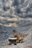 Iron ore opencast. Heavy mining dump trucks are being loaded with iron ore on the opencast mining with stormy clouds on the background Stock Photography