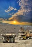 Iron ore opencast mining. Excavator loading iron ore into heavy dump trucks on the opencast on sunset Stock Images