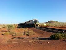Iron Ore train in the outback Pilbara Western Australia. Iron Ore trains in the Pilbara of Western Australia can be 2 kilometres long Stock Photo