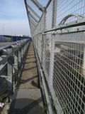 Iron Perspective. Perspective effect of a protected walkway on a highway bridge Royalty Free Stock Photo
