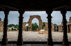 Iron Pillar viewed through cloister columns at qutb complex. It is the world's foremost metallurgical curiosities. Iron pillar is 7.21-metre high and weighing Stock Images