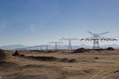 Iron pillars with electric wires in the desert against the backg Stock Photo