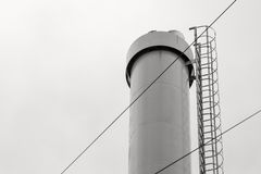 Iron pipe with a side ladder against the sky Royalty Free Stock Image