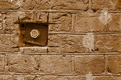 Iron plate and nut on a brick wall Stock Photo