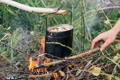 Iron pot cooks soup over open fire in a campsite Royalty Free Stock Image