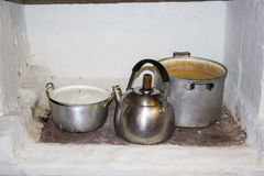 Iron pots, kettle for cooking on the fire stove in the kitchen. In the old house in the village Stock Photos