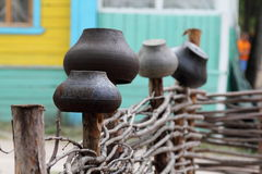 Iron pots on a wicker fence. The rural landscape. The wicker fence hang iron pots Royalty Free Stock Photography