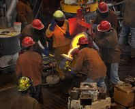 Iron Pour - Filling the Cup. Crowd of workers gather around to fill the cup from the bull ladle Stock Images
