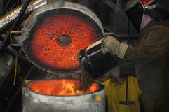 Iron Pour - Loading the Furnace. Protected workman loads buckets of scrap metal into iron furnace Royalty Free Stock Photos