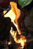 Iron Pour - Mold on Fire. Workers pour molten iron into mold which catches fire Stock Images