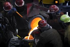 Iron Pour - Workers Gather Around. Bull ladle to cup fill - focus on bull ladle stock photos