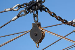 Iron pulley block. Hanging on a chain of a fishing boat Royalty Free Stock Photography