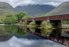Iron rail bridge scottish highlands. An iron rail bridge reflected in loch awe in the scottish highlands Royalty Free Stock Images