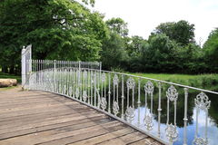 Iron railing on bridge. An old, small, arched wooden bridge over a river with a fancy white wrought iron railing and gates surrounded by trees and parkland Stock Image