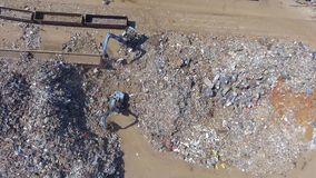 Iron raw materials recycling pile, work machines. Metal waste junkyard. Excavators diggers works on a garbage dump .View from stock footage