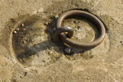 Iron ring set in concrete. Iron mooring ring set in concrete. Closeup Royalty Free Stock Image