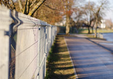 Iron rods fence along paved path Royalty Free Stock Image