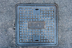 Iron roman manhole cover on the street Stock Photography