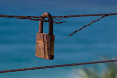 Iron rope with padlock. Closed padlock on cut iron rope represents insecurity Stock Image