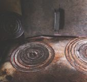 Iron circles on the old rural stove. Stock Photos