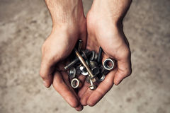 Iron rusty tools bolts and screws in mans hands. Stock Image