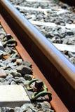 Iron rusty train railway detail over dark stones. Rail way royalty free stock photo