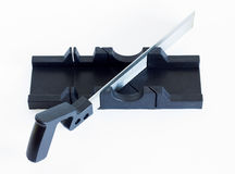 An iron saw and a miter box. A saw from metal with a plastic handle is standing in a miter box Stock Photos