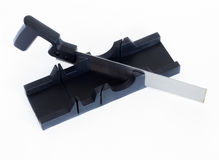 An iron saw and a miter box. A saw from metal with a plastic handle is standing in a miter box Stock Images
