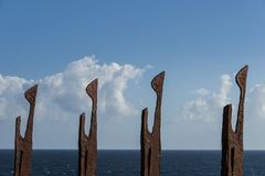 Iron sculpture. Row of iron sculptures against blue sky stock images