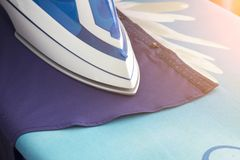 Iron, shirt, ironing board, close-up royalty free stock photography