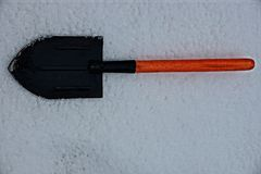 A small black shovel lies on the snow. Iron shovel with a wooden handle on white snow on the street Royalty Free Stock Photo
