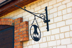 Iron sign indicating the pottery workshop. On a brick wall Stock Images