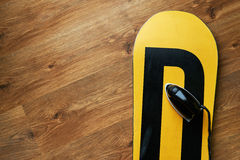 Iron on a snowboard wax, lying  wooden floor Royalty Free Stock Image